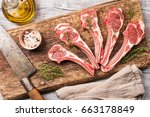 Small photo of Raw lamb chops with salt, pepper and herbs over white wooden background with vintage chef knife near. Top view.