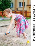 Small photo of The girl is fondling a sandbox. The concept of lifestyle and childhood.