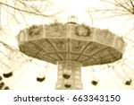 Small photo of Blurry defocused photo of chain carousel in motion. Dreamy nostalgia background. Sepia.