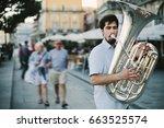 street musician playing tuba... | Shutterstock . vector #663525574
