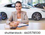 female car dealer in showroom  | Shutterstock . vector #663578530
