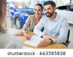 young couple with car dealer in ... | Shutterstock . vector #663585838