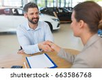 car dealer shaking hand with a... | Shutterstock . vector #663586768