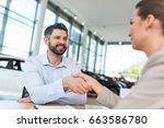car dealer shaking hand with a... | Shutterstock . vector #663586780