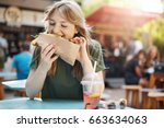 Hungry freckled blonde girl eating taco on a food court on a sunny summer day in park.