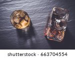 whiskey glass on dark stone... | Shutterstock . vector #663704554