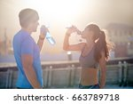 active fitness couple hydrating ... | Shutterstock . vector #663789718