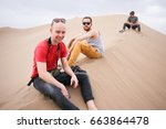 Small photo of dasht e kavir desert, Iran - April 18, 2017: Three unidentified male tourists are sitting on the sand dune in the background of big beautiful dasht e kavir desert dunes near Yazd, Iran