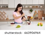 woman pouring tea into the... | Shutterstock . vector #663906964