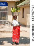 Small photo of LILONGWE, MALAWI - SEPTEMBER 05 2009: An African Malawian woman carries corn in a basin on her head. Women in Malawi are able to carry and balance heavy loads on their heads for long distances.