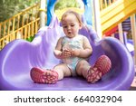 One Year Old Little Baby Girl Playing At Playground Outdoors In Summer - stock photo