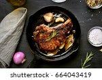 roasted pork steak in frying... | Shutterstock . vector #664043419