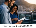 two smiling coworkers using a...   Shutterstock . vector #664137220