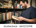 curious man choosing book in... | Shutterstock . vector #664151908