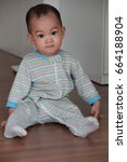 Small photo of 10 months Asian baby boy in Infant Romper Jumpsuit sitting on wooden floor.look like door.