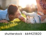 Stock photo man playing with puppy on grass with girlfriend pet bonding best friend healthy outdoor lifestyle 664425820