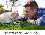 Stock photo pet owner bonding with puppy in park on grass playing petting affection love best friends 664427290