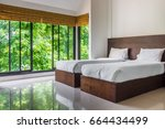 Small photo of Modern master bedroom with twin beds and wide glass windows. The design to give scenic view of natural outdoor garden.