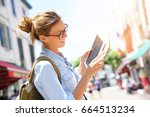 happy tourist girl reading map... | Shutterstock . vector #664513234