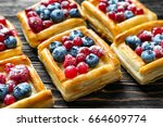 Small photo of Delicious puff pastries with berries and sugar powder on wooden background