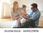 Happy Family Sitting On Floor...