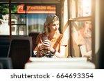 young teenage girl using her... | Shutterstock . vector #664693354