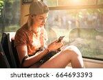 young teenage girl using her... | Shutterstock . vector #664693393