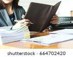 businesswoman holding a brown... | Shutterstock . vector #664702420
