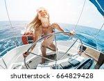young happy woman steering... | Shutterstock . vector #664829428