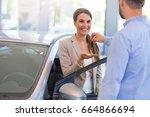 woman receiving car keys from a ... | Shutterstock . vector #664866694