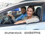 young couple sitting in a car   | Shutterstock . vector #664869946