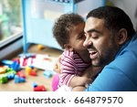 father lets daughter playing... | Shutterstock . vector #664879570