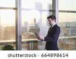 young businessman standing and... | Shutterstock . vector #664898614