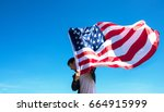 man is holding waving american... | Shutterstock . vector #664915999