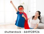 Small photo of happy lovely little girl wearing superhero clothing making ready to fly posing and looking at camera smiling in living room with beautiful young mother.