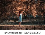 Small photo of Slavery. Very cute young girl with a blindfold red ribbon. Doll appearance. Woman with brown hair in a turquoise dress on nature. Long hair. Natural light. Model posing on the nature. Kidnapping