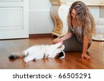 Stock photo woman playing with a cat 66505291