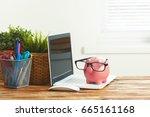 piggy money box with laptop on... | Shutterstock . vector #665161168
