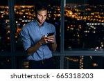 young businessman using a... | Shutterstock . vector #665318203