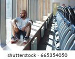 Small photo of Restful sportsman looking through window during rest after workout