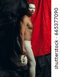 Small photo of Arty portrait of circus performer in tights holding venetian mask (volto bianco), posing over black and red cloths. Muscular body and perfect tan. Studio shot