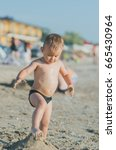 Small photo of child breaks leg mound of sand on the beach in a speedo