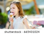 adorable little girl eating... | Shutterstock . vector #665431024