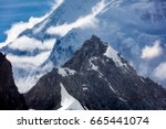 Small photo of Clouds pass over and around snowy mountain peaks of Alaska Range in Alaska