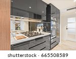 Stock photo black color pantry cupboards giving a shiny look beside the closed door there are a stove and a 665508589
