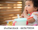 baby eating baby food | Shutterstock . vector #665670034