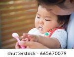 baby eating baby food | Shutterstock . vector #665670079