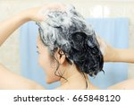 woman washing her hair. | Shutterstock . vector #665848120