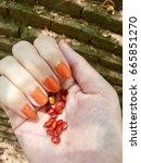 Small photo of orange nails and orange seed