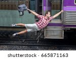 Small photo of Man with backpack flies behind a moving train. Tourist holding a moving train from a railway station. Funny traveler catches the train in motion.Journey to the last minute.
